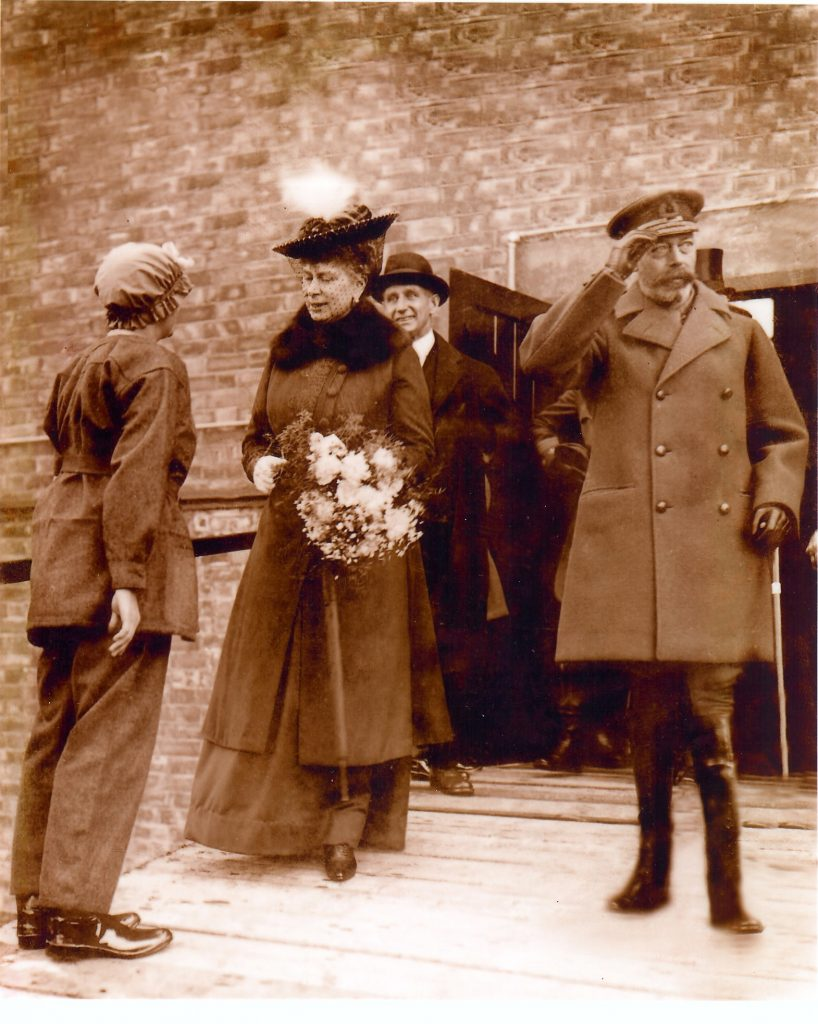 A munitions worker, Victoria May McIver, is pictured giving Queen Mary a bouquet of flowers. The king stands next to his wife.