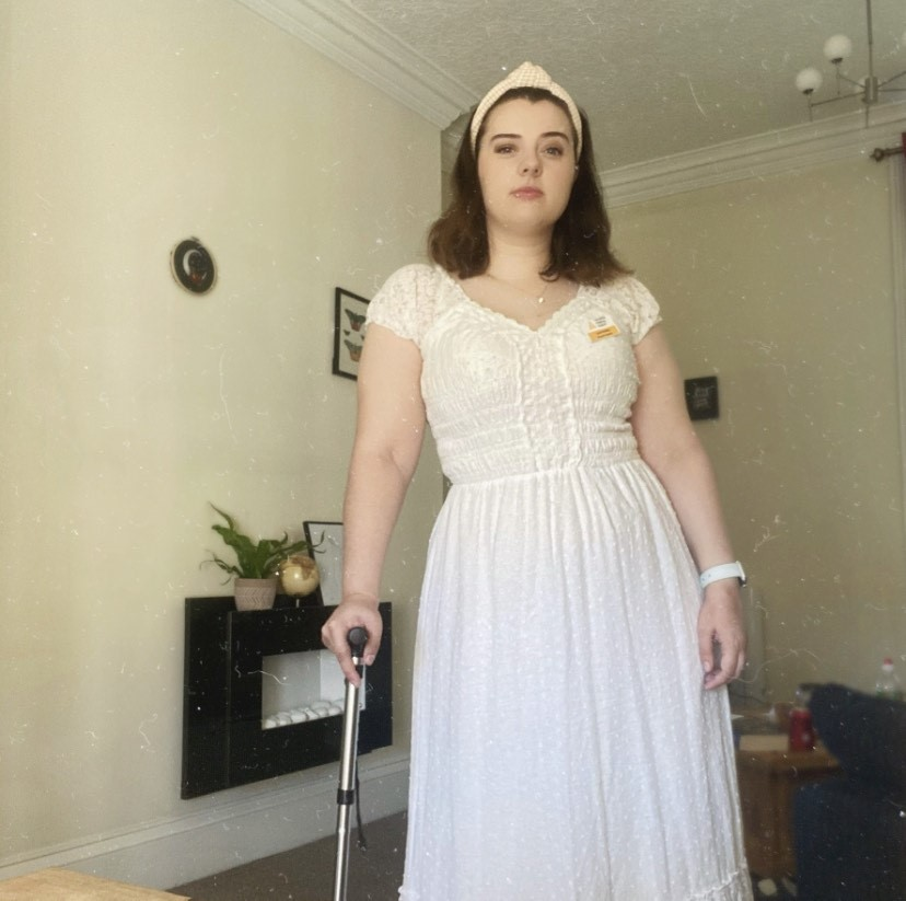Laura is pictured in a white dress, holding a mobility aid for support.